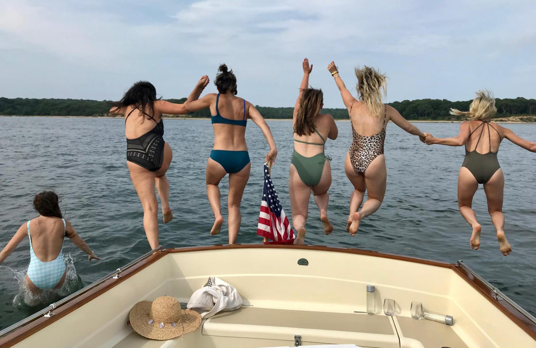 Women jumping off the back of a boat during a private charter near the Hamptons.